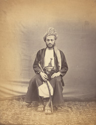 Full-length seated portrait of the Imam of Muscat.